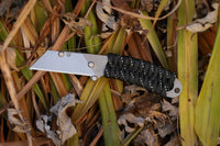Banzelcroft Customs MEK, a titanium EDC utility knife with glow tracer paracord wrapped handle.