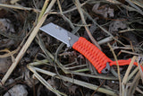 Banzelcroft Customs MEK, a titanium EDC utility knife with hunter's orange paracord wrapped handle.