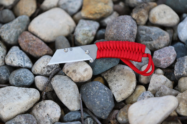 Banzelcroft Customs MEK, a titanium EDC utility knife with a red paracord wrapped handle.
