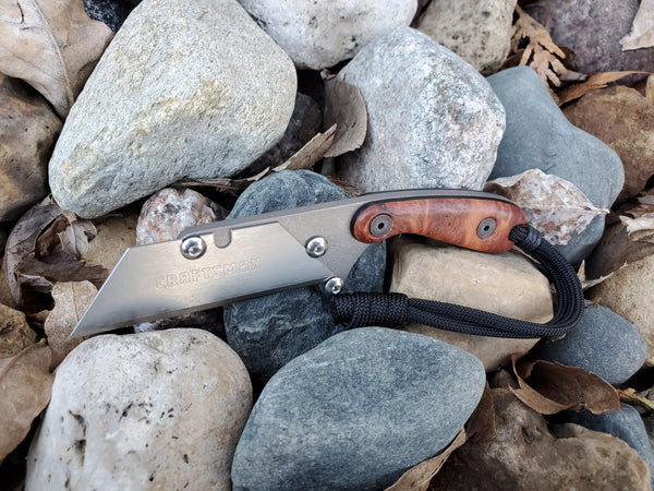 Banzelcroft Customs mini MEK, a titanium EDC utility knife with red coolibah burl and black liner.
