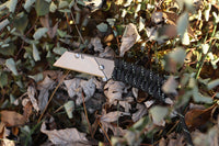 Banzelcroft Customs MEK, a titanium EDC utility knife with a reflective tracer paracord wrapped handle.