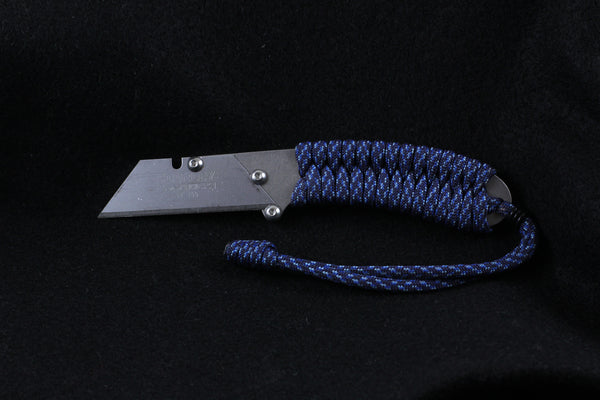 Banzelcroft Customs MEK, a titanium EDC utility knife with a speckled blue paracord wrapped handle.