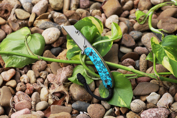 Banzelcroft Customs MEK, a custom titanium EDC utility knife with turquoise and black web trustone and brass liner handle scales.