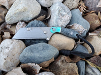 Banzelcroft Customs mini MEK, a titanium EDC utility knife with denim micarta and turquoise acrylic handle.
