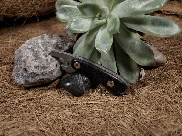 Titanium bottle opener with black G10 and red liner handle.
