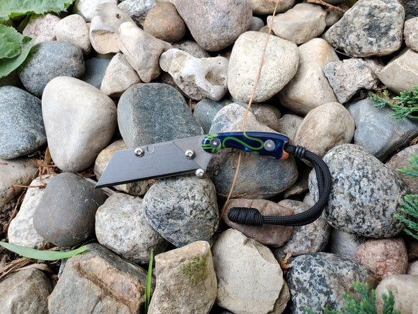 Banzelcroft Customs MEK, a titanium EDC utility knife with a blue, green, and orange acrylic handle.