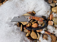 Banzelcroft Customs mini MEK, a custom titanium EDC utility knife with stabilized curly koa handle scales.