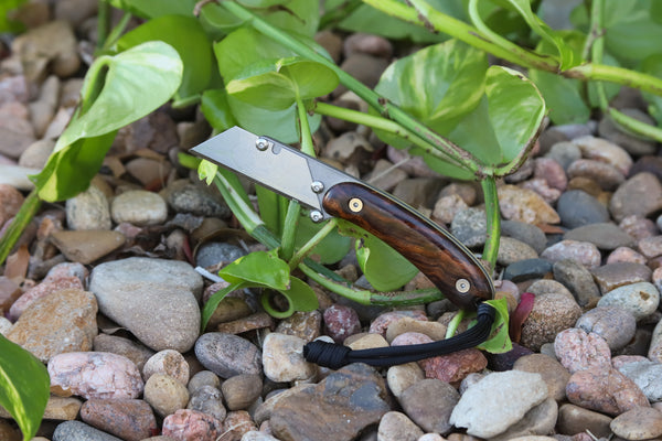Banzelcroft Customs MEK, a titanium EDC utility knife with figured ironwood and brass handle scales.
