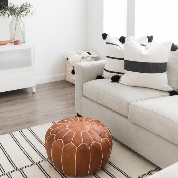 Woven Nook Moroccan Pouf next to couch