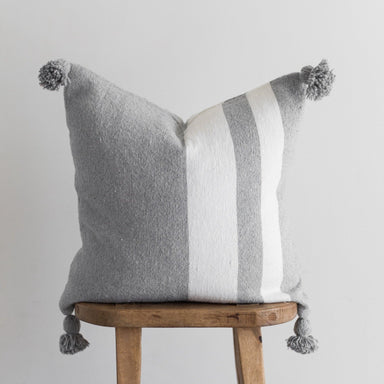 "22"" Moroccan Pom Pillow with a gray base color and two thick white stripes"