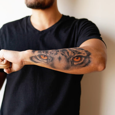 tiger eyes forearm tattoo