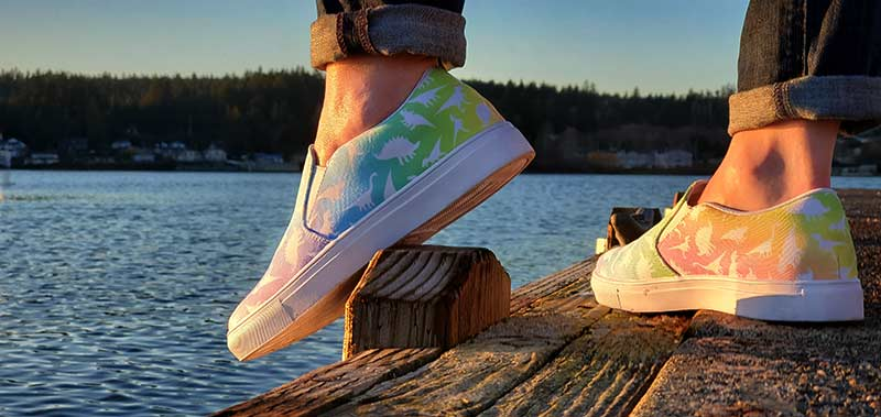 Woman wearing rainbow print women's dinosaur slip on sneakers on dock