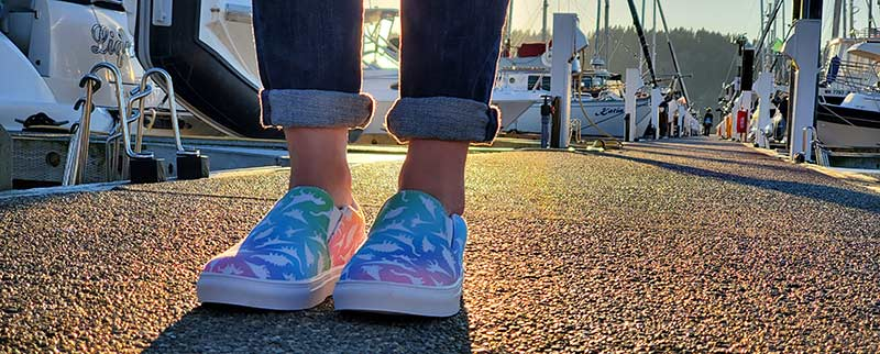 Woman wearing rainbow dinosaur print sneakers on dock