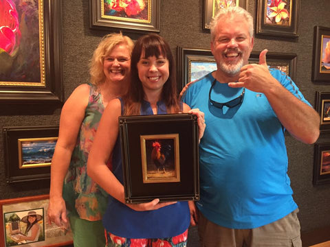 Karen Whitworth with collectors at Tabora Gallery Kauai Hawaii holding Origianl Oil Painting of Rooster