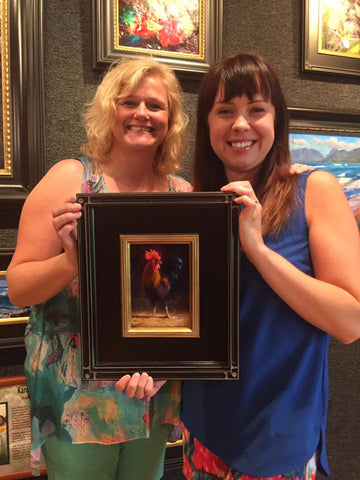 Karen and Collector Kerry posing with framed rooster painting at Tabora Gallery in Kauai Hawaii