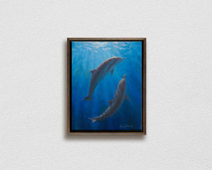 Framed ocean art on canvas of 2 Spinner Dolphins by Hawaii whale artist Karen Whitworth hanging on white wall