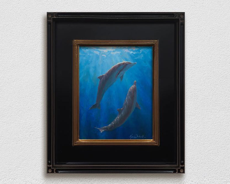 Framed underwater whale art canvas of 2 Spinner Dolphins by Hawaii artist Karen Whitworth hanging on white wall