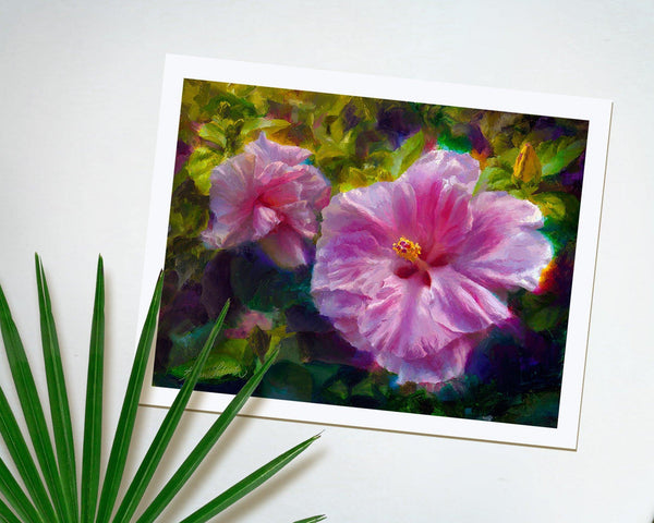 Wall art print of tropical pink hibiscus flowers by Hawaii artist Karen Whitworth on white table with palm frond