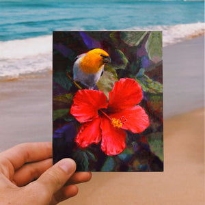 Hand holding an envelope and card featuring art of a tropical Hawaiian Hibiscus flower and an endemic Palila bird on beach background
