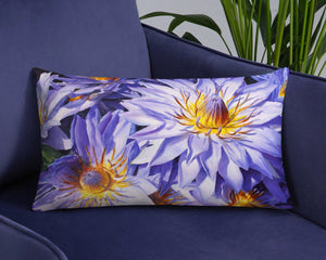 Lumbar throw pillow with blue and purple flowers on a plush arm chair