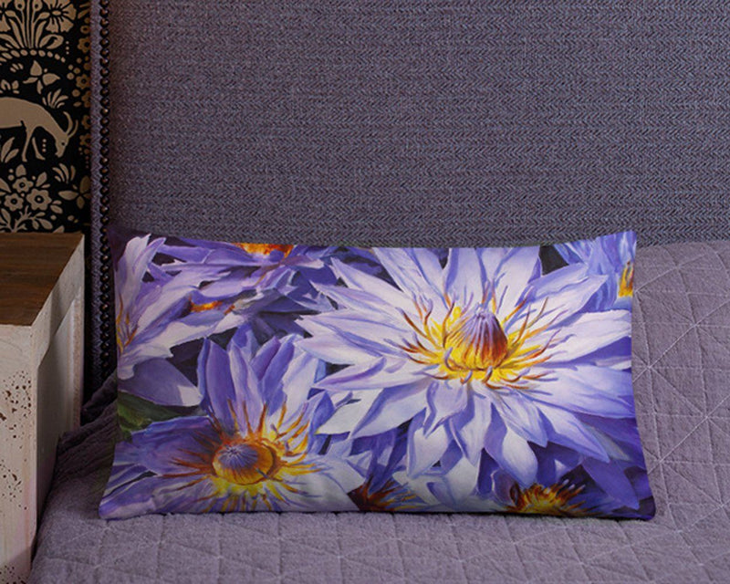 Lumbar throw pillow with blue and purple flowers sitting on bed