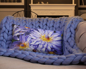 Cozy blanket and lumbar throw pillow with tropical blue and purple flowers sitting on a couch