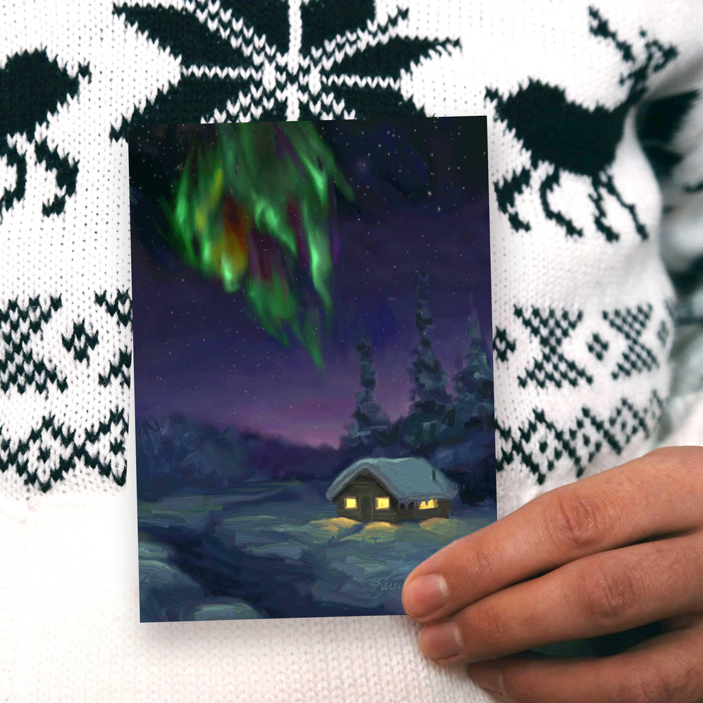 Northern lights greeting card with snowy log cabin by Alaska artist Karen Whitworth.