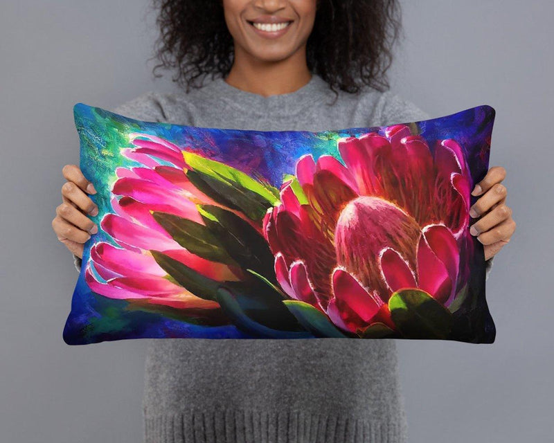Woman holding reversible lumbar throw pillow with pink and red tropical protea flowers