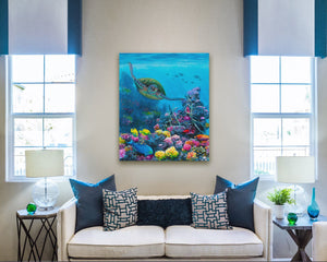 Ocean wall art canvas of green sea turtle swimming through a coral reef with tropical fish hanging on wall above white couch with turquoise blue pillows