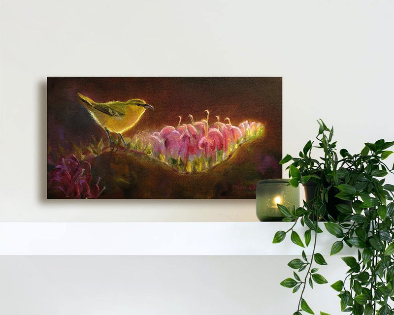 Wall Art Canvas Print of Hawaiian Amakihi Bird and Koli'i Flowers Endemic to the tropical islands and painted by Gallery Artist Karen Whitworth. The painting is sitting on a shelf with a potted plant and candle.