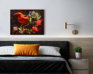 Wall art canvas of Hawaiian Iiwi bird on an Ohia Lehua tree. Painting by Tropical Artist Karen Whitworth. Painting is on a white wall with a bed and nightstand below it.