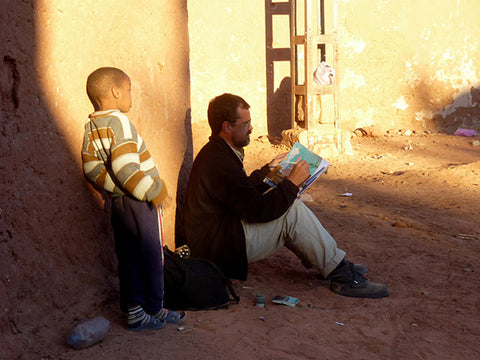 Enrique Flores sketching in Morocco viewed by a child