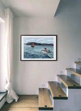 Load image into Gallery viewer, Boat navigating with lighthouse in background by Mariscal.  Print with margin framed in black wood