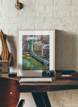Load image into Gallery viewer, A mixed of activities in a green city painting by Clara Leon.  Print with margin framed in natural wood