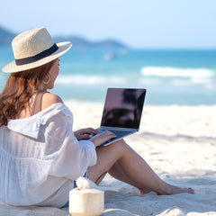 image of the back of a woman sitting facing the ocean with an open laptop