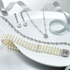 image of wedding style items laid out including freshwater cultured pearl and diamond earrings, pave and bezel diamond necklace, floral motif diamond bracelet and triple-strand cultured pearl and diamond bracelet