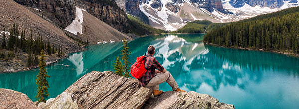 Man sitting on a rock looking out over lake