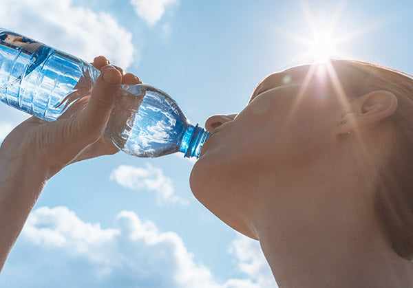Woman drinking a bottle of water in the sun.