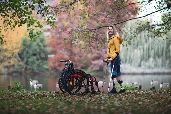 Girl with prosthetic legs in park with wheelchair
