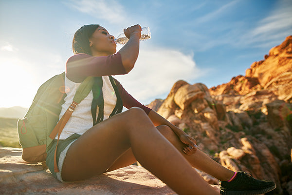 Woman drinking water while hiking.