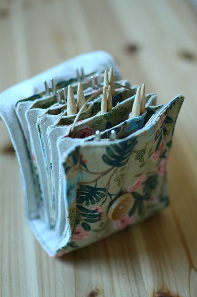 Interchangeable knitting needle storage with a zipper pocket