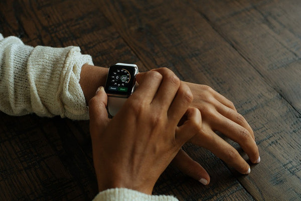 woman pressing button on apple watch
