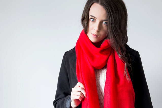 Model wearing a crimson red 100% cashmere wrap scarf handmade in Nepal with ethically sourced wool