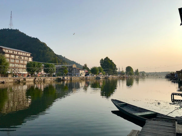 Mirror-like surface of Dal Lake in Srinagar with a shikara in the foreground and looking out to the lakeside road