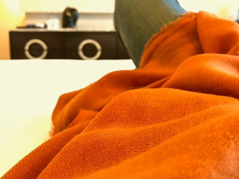 Relaxing on hotel bed draped in the Copper Orange AUTHENTIC pashmina shawl by Ethical Cashmere