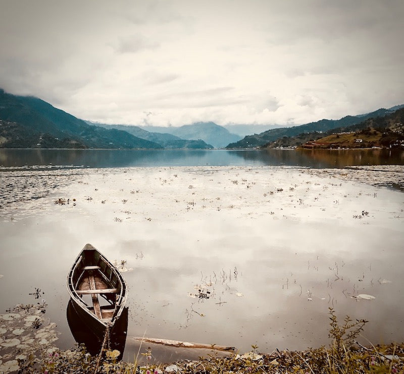 Traditional Nepali small wooden boat tied to the bank of the still waters of Phewa Lake looking out to the mountains of Annapurna