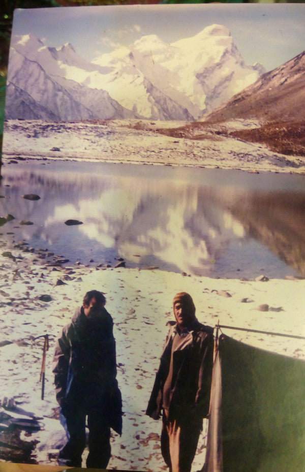 Two Kashmiri trekking guides posing in front of a mountain lake reflecting a snowy Himalayan peak
