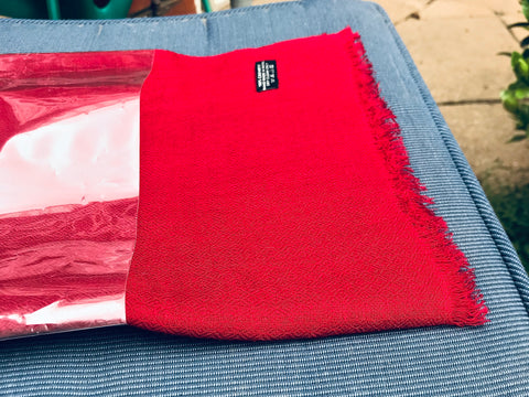 Red pashmina scarf folded on a chair in bright sunlight | AUTHENTIC cashmere scarf by Ethical Cashmere