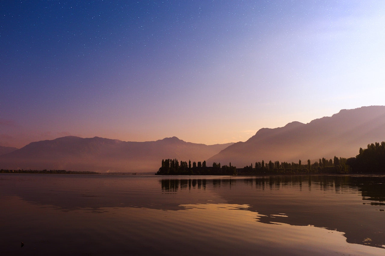 Glassy mirrored lake surface in Srinagar, with the Western Himalayas in the background