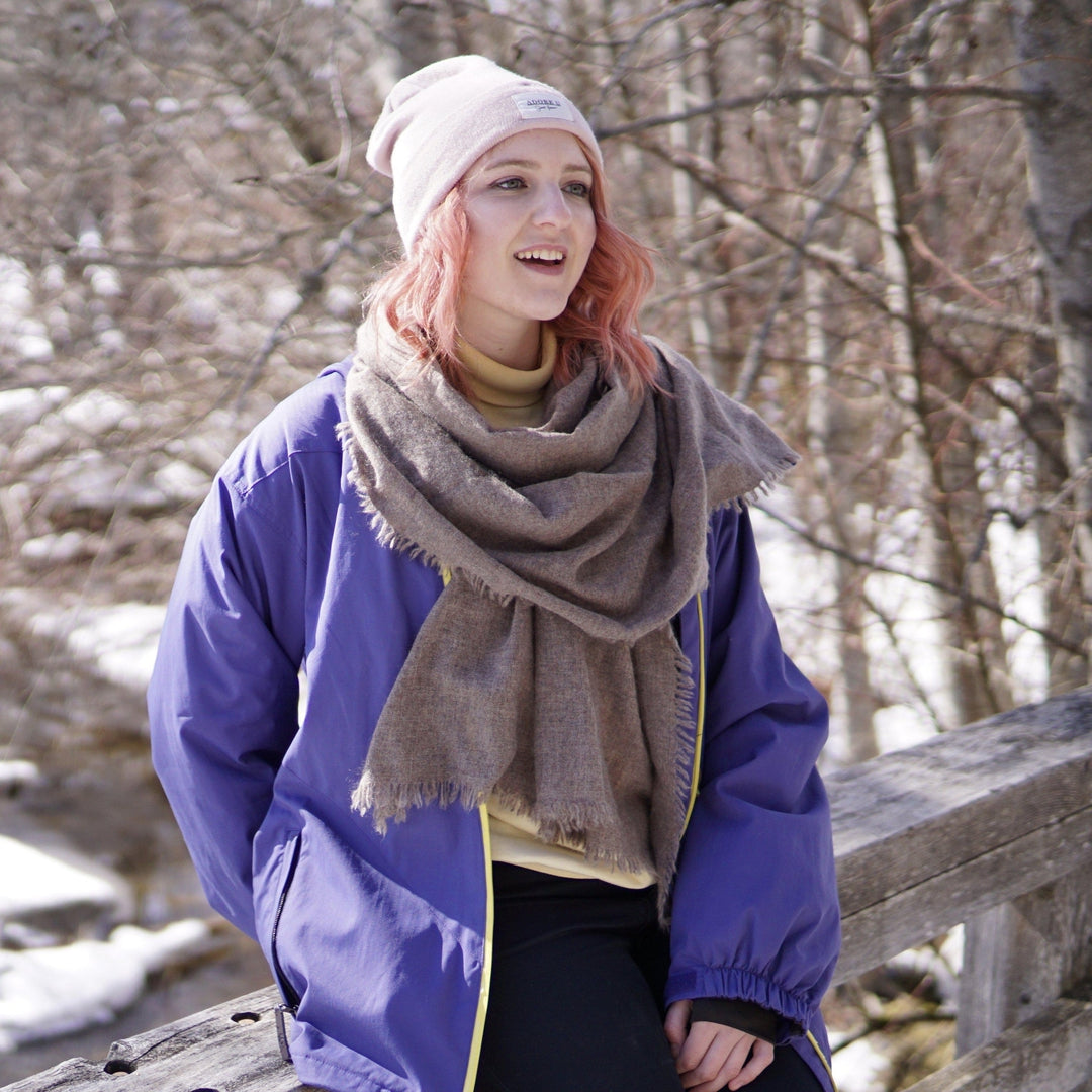 Ethical cashmere natural dye high grade cashmere scarf in dark taupe grey, worn loosely draped over the chest